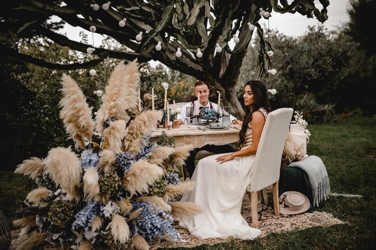 Bride and groom sitting at their bohemian elopement  sweetheart table