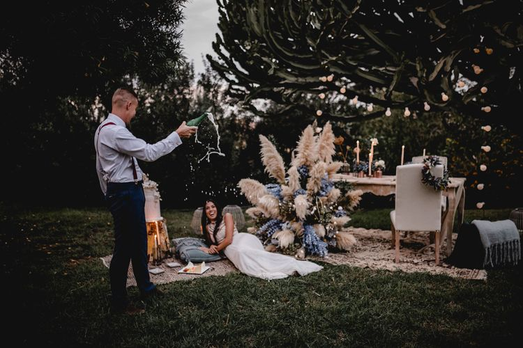 Popping champagne at bohemian elopement wedding