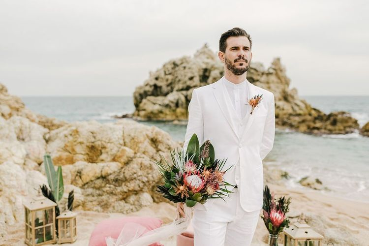 Groom in White Wedding Suit and Grandad Shirt Holding His Brides Protea Wedding Bouquet