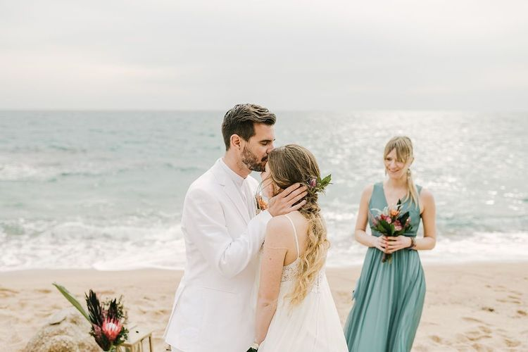Groom in White Wedding Suit Kissing His Bride in a Beach Wedding Dress