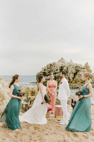 Intimate Beach Wedding Ceremony with Groom in White Suit, Bride in Spaghetti Strap Wedding Dress and Bridesmaids in Green Dresses