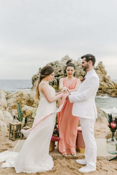 Hand Fastening Wedding Ceremony with  Groom in White Wedding Suit and Bride in Floaty Beach Wedding Dress