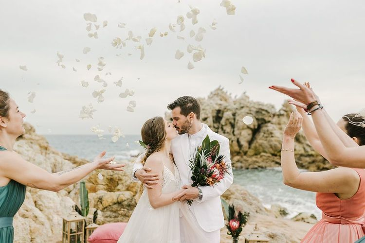 Confetti Moment on the Beach with Bride in Beach Wedding Dress and Groom in White Wedding Suit