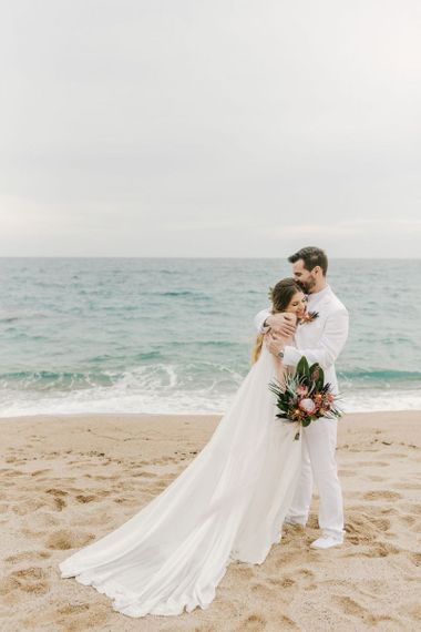 Bride in Beach Wedding Dress and Groom in White Wedding Suit Embracing on the Beach