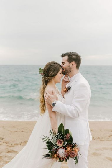 Groom in White Wedding Suit and Bride in Floaty Wedding Dress Hugging on the Beach