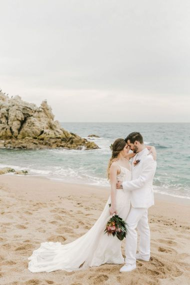Groom in White Wedding Suit and Bride in Floaty Wedding Dress Embracing on the Beach