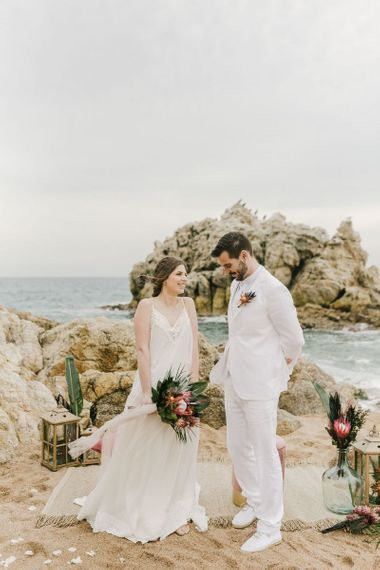 Bride in Beach Wedding Dress and Groom in White Wedding Suit Standing at their Wedding Ceremony Spot