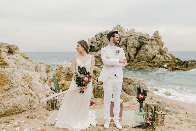 Groom in White Wedding Suit and Bride in Spaghetti Strap Wedding Dress Standing at Their Wedding Altar