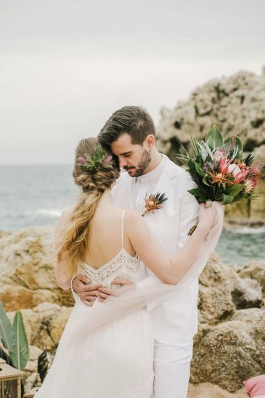 Groom in White Suit Embracing His Bride in a Boho Wedding Dress