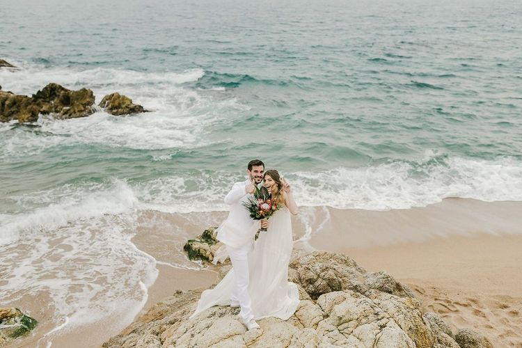 Bride and Groom Standing on the Cliffs of Their Beach Wedding