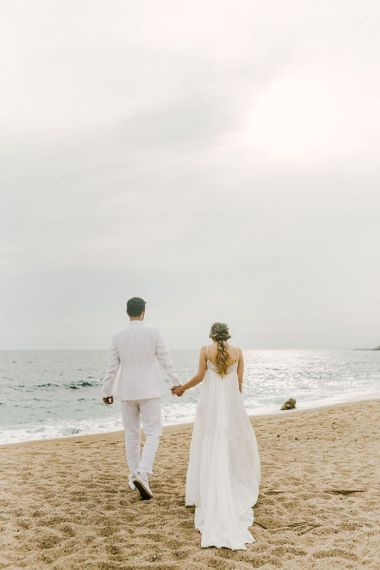 Groom in White Wedding Suit and Bride in Boho Wedding Dress Hand in Hand Walking Along the Beach