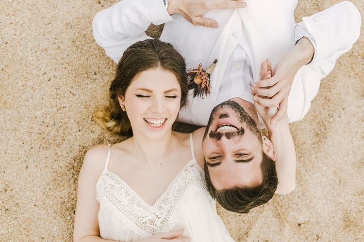 Bride and Groom Laying in the Sand on the Beach