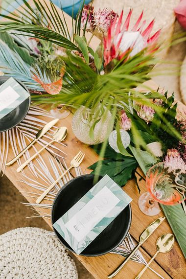 Tropical Sweetheart Table with Palm Leaves, Gold Cutlery and Protea Wedding Flowers