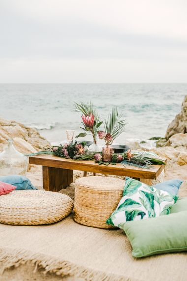Intimate Sweetheart Table on the Beach with Wicker Pouffes and Cushions
