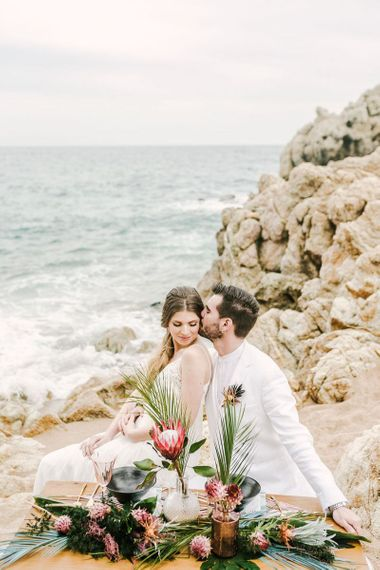 Bride and Groom Kissing at Their Intimate Sweetheart Table