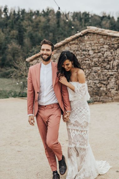 Bride in off the shoulder Grace Loves Lace Dress with groom in Coral Suit