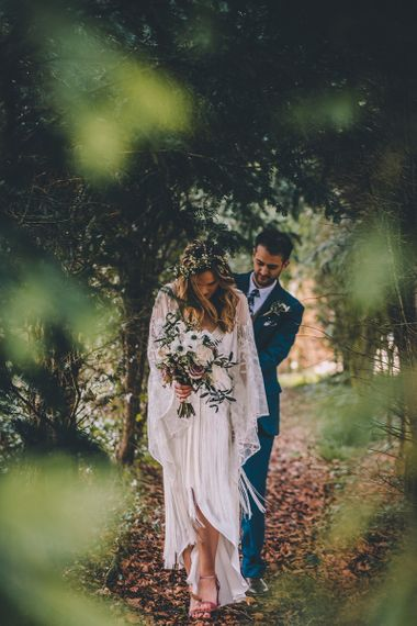 Bride and groom walking through the trees in boho wedding dress