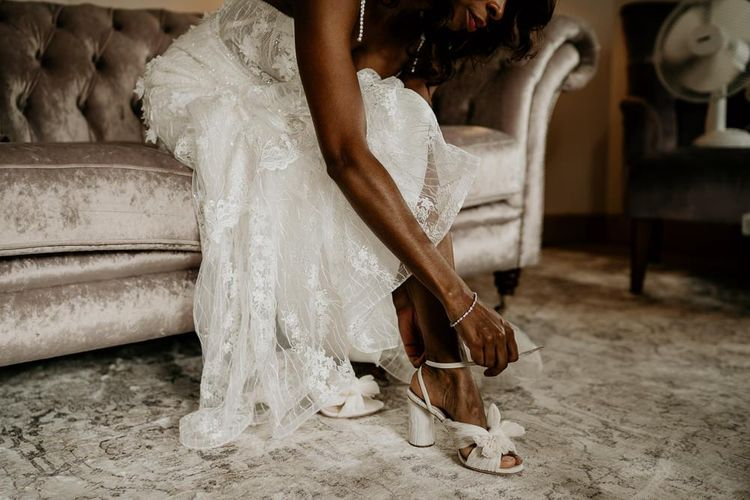 Nigerian bride putting on her wedding shoes with bows