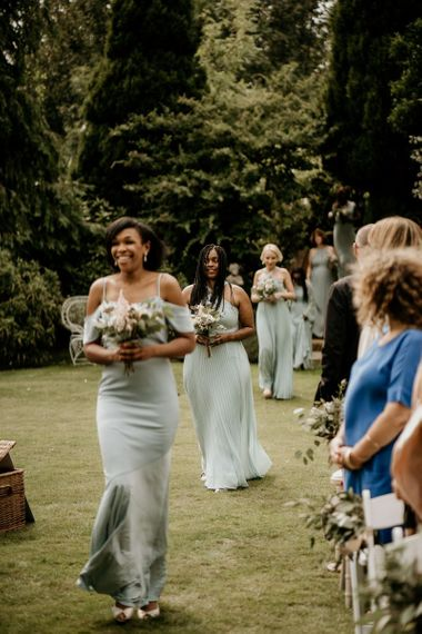 Bridesmaids in pale green dresses walking down the aisle