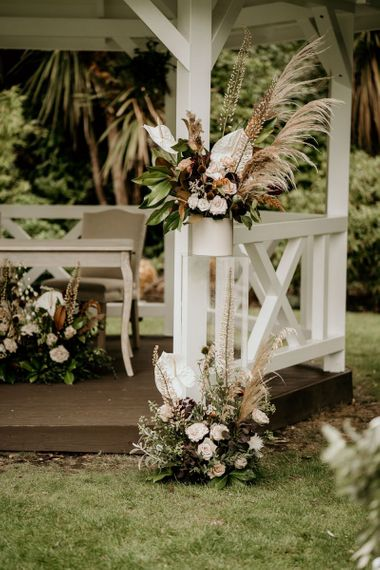 Wooden gazebo altar flowers with pampas grass, pink roses and white Anthuriums