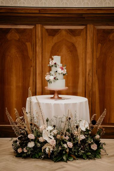 Wedding cake table decorated with floral arrangement