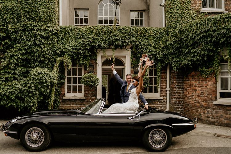 Nigerian bride and Irish groom sitting on top of a convertible E-Type Jaguar wedding car