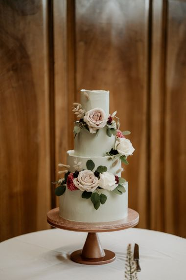 Four tier green wedding cake decorated with pink wedding flowers