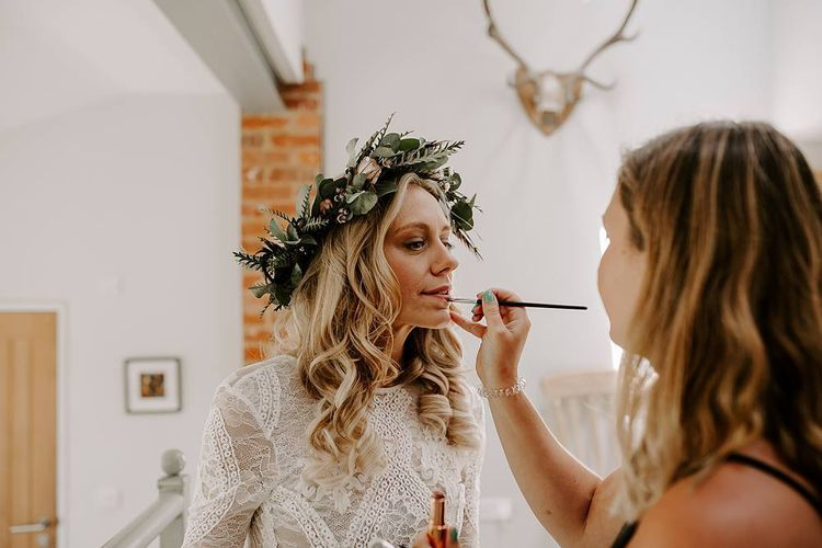 Finishing touches for bride wearing flower crown