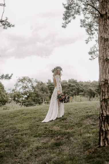 Bride in low back wedding dress with flower crown and Protea bouquet