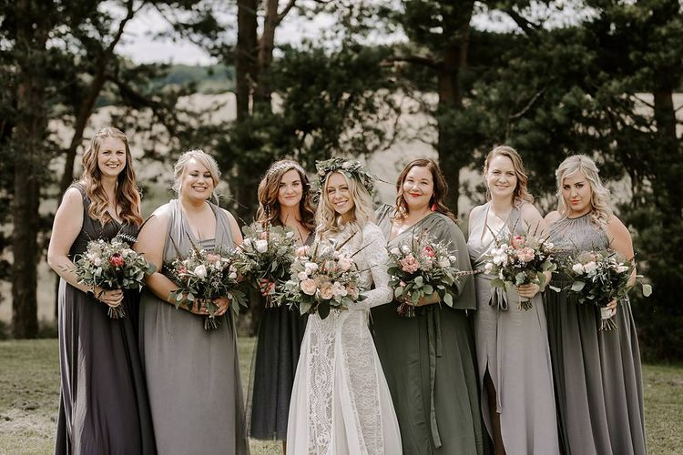 Bridesmaids in grey dresses clutch Protea bouquet