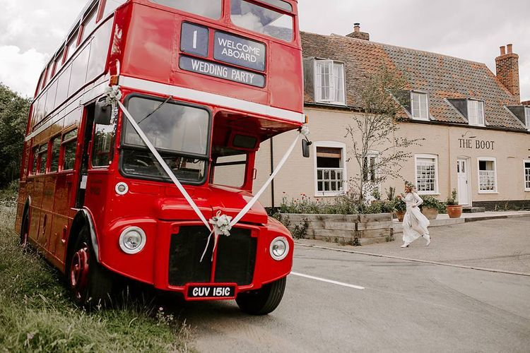 Bride makes her way onto red bus wedding transport