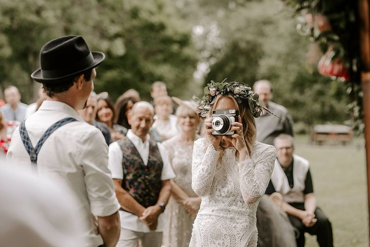 Bride takes a photo of her groom at the altar