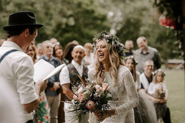 Bride laughs during ceremony holding a Protea bouquet