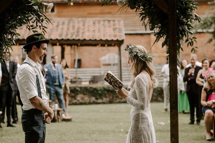 Bride reading her wedding vows during outdoor ceremony