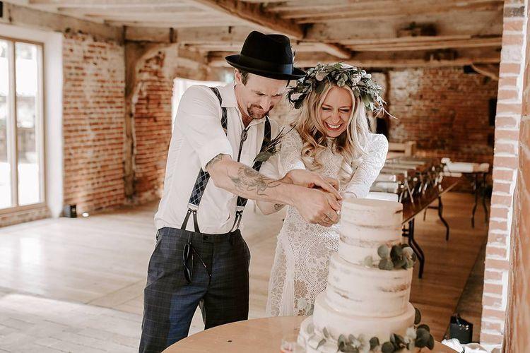 Bride and groom cut the rustic wedding cake