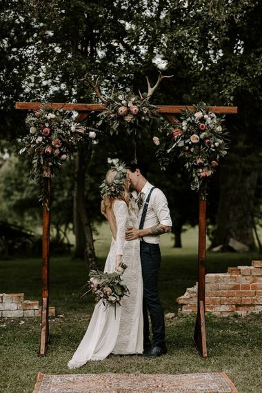 Bride clutches Protea bouquet as she kisses groom under wooden arch decorated in flowers