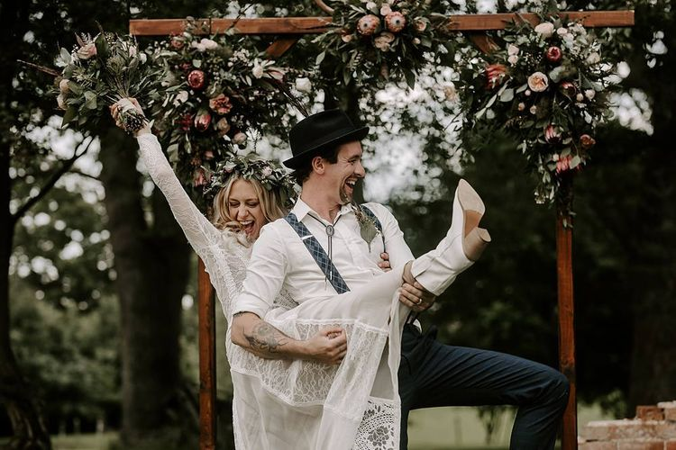 Groom plays guitar on brides leg who clutches Protea bouquet and wears bridal boots
