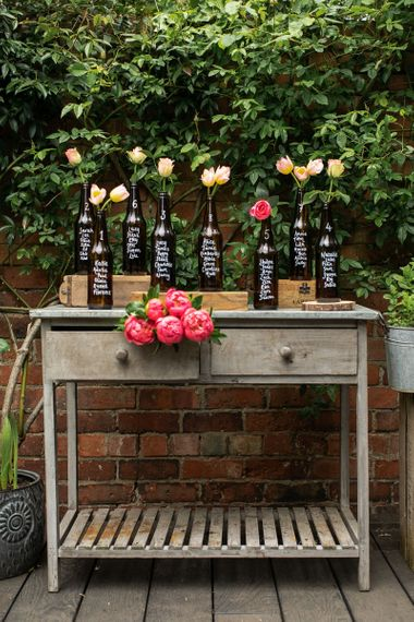Table plan created out of eight brown beer bottles, rustic crates and beautiful flowers, all resting upon a limewashed occasional table