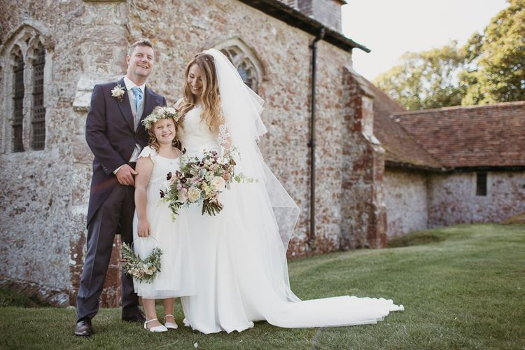 Bride in Lace St Partrick Wedding Dress and Groom in Morning Suit  with Their Flower Girl