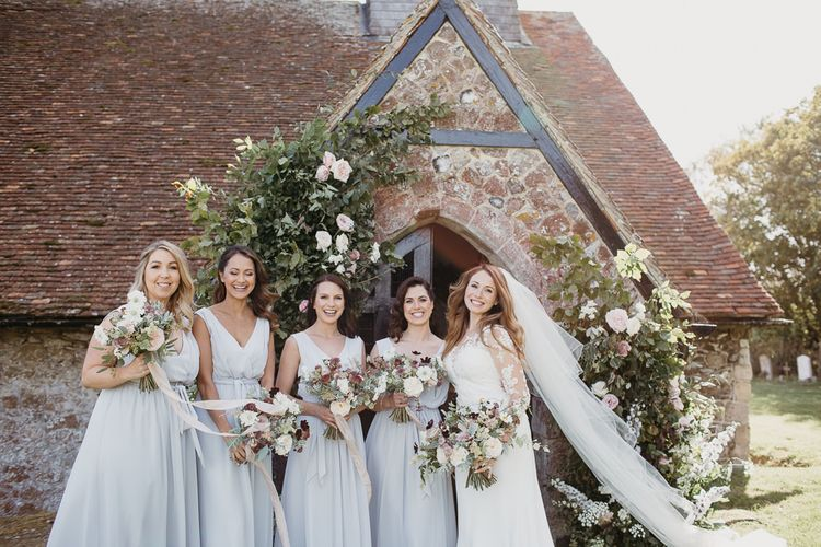 Bridal Party Standing in Front of the Church Entrance with Bridesmaids in Grey Dresses and Bride in Lace Wedding Dress