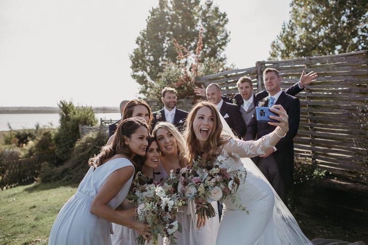 Bridal Party Taking a Selfie with the Groomsmen in the Background