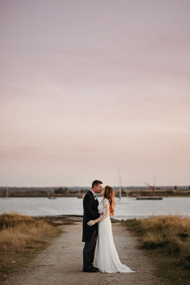 Bride in St Patrick Wedding Dress and Groom in Traditional Morning Suit Embracing by the Swale estuary