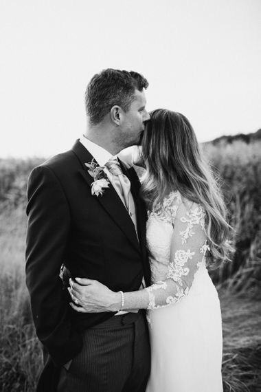 Groom in Traditional Morning Suit Kissing His Brides Forehead