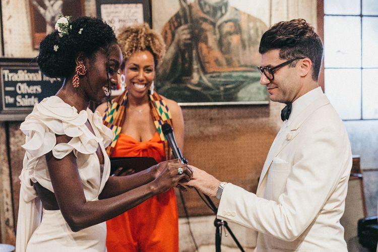Stylish Bride and Groom in Ruffled Wedding Dress and White Tuxedo Jacket Exchanging Wedding Rings