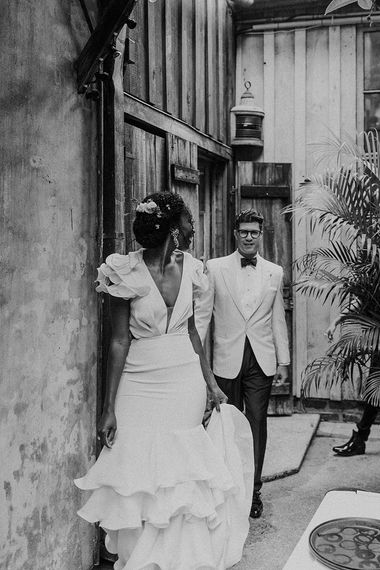 Stylish Bride in Secondhand Johanna Ortiz Wedding Dress with Ruffled Sleeves and Skirt and Groom in White Tuxedo Jacket and Bow Tie