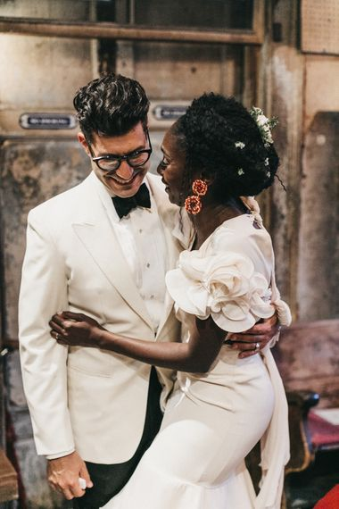 Stylish Bride in Johanna Ortiz Wedding Dress with Ruffled Shoulder Detail Embracing Her Groom in a White Tuxedo Jacket