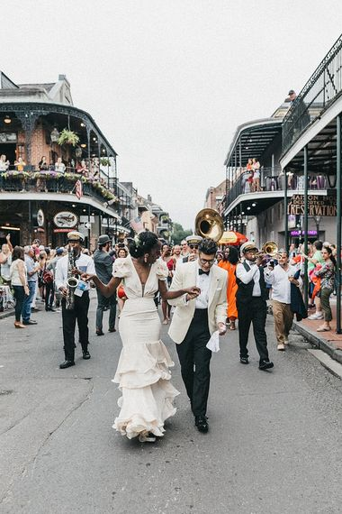 Stylish Bride and Groom in Johanna Ortiz  Wedding Dress and White Tuxedo Jacket Walking Down the Street with a Brass Band Procession Following Them