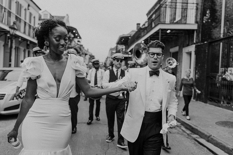 Stylish Bride and Groom in Johanna Ortiz  Wedding Dress and White Tuxedo Jacket Walking Down the Street with a Brass Band