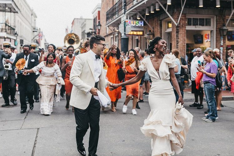 Stylish Bride and Groom Walking Down the StreetFollowed by A Brass Band Procession and Their Wedding Guests