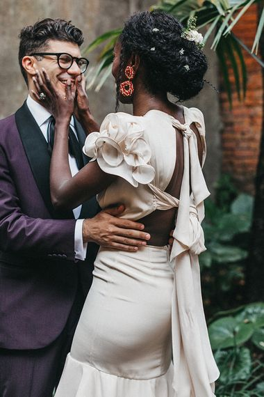 Bride in Johanna Ortiz Wedding Dress with Tie Up Back Detail and Ruffle Sleeves  Holding Her Grooms Face